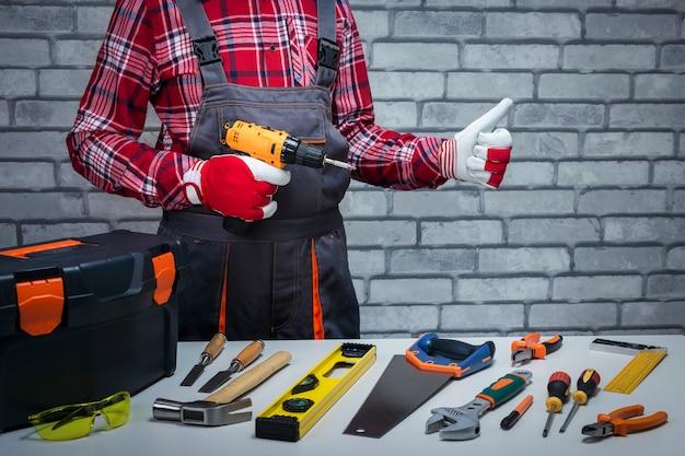 일할 준비가 된 핸디. 엄지손가락을 몸짓으로 다른 도구와 수리공입니다. 수리 개념입니다.