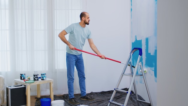 Handyman renovating house. painting wall with roller brush dipped in white paint. handyman renovating. apartment redecoration and home construction while renovating and improving. repair and decoratin