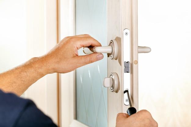 便利屋はドアロックを修理します。新しいドアロックを取り付ける労働者の手のクローズアップ。