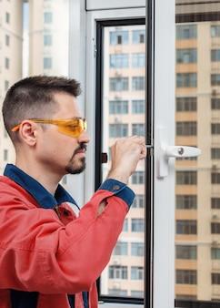 Разнорабочий устанавливает пластиковое окно