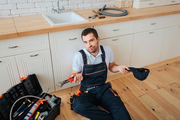 Handyman sit on floor in kitchen
