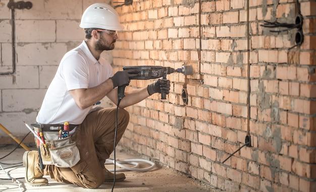 便利屋は、建設現場での設置、専門労働者のために削岩機を使用しています。電気技師と便利屋の概念。