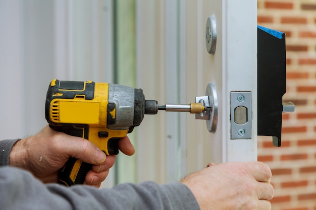 Handyman using a drill to installing lock in door in a house