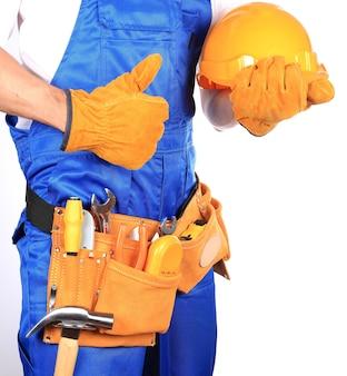 Разнорабочий со шлемом и рабочим поясом, полным инструментов, изолированные на белом фоне