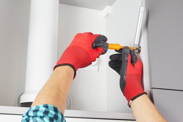 스크루 드라이버로 핸디가 부엌에 가구를 설치합니다. 작업자는 회색 캐비닛에 문을 설정합니다.