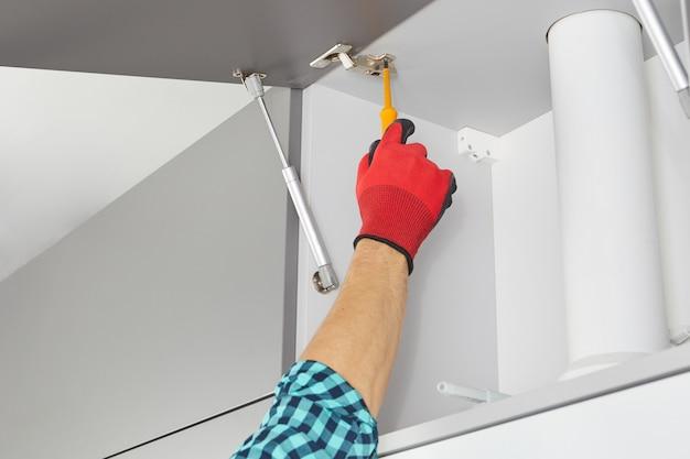 ドライバーを持った便利屋がキッチンに家具を設置労働者が灰色のキャビネットにドアを設置