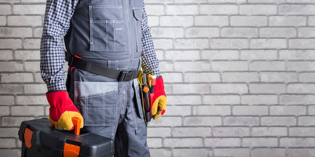 Handyman with toolbox and tool belt against brick wall surface with copy space. banner. repair service.