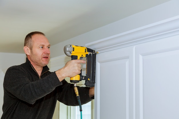 Handyman working instal brad nail gun to crown moulding wall cabinets framing trim