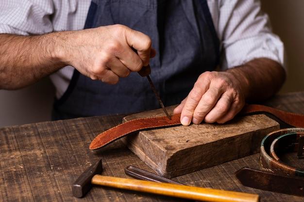 Разнорабочий работает над кожаным ремнем, вид спереди