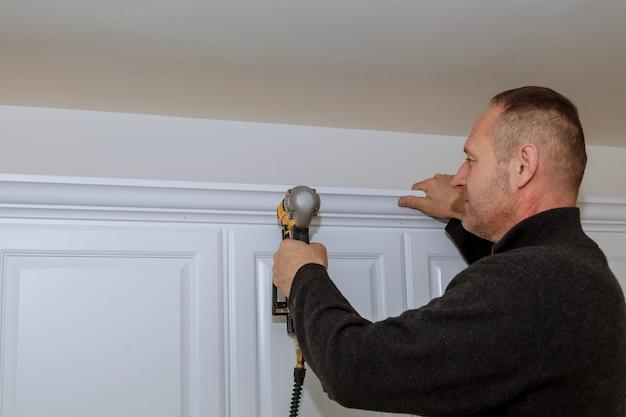 Handyman working using brad nail gun to crown moulding on white wall cabinets framing trim,