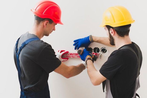 Handymen installing plug with level