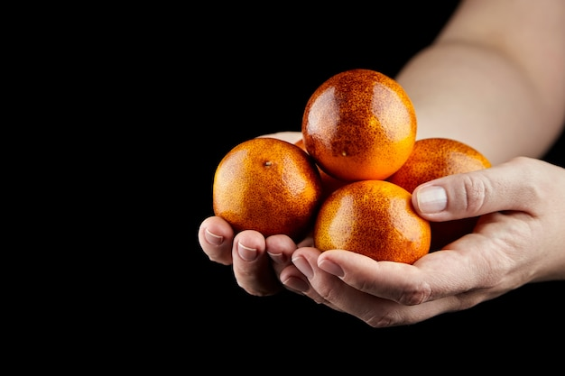 Hanful of whole red oranges on black wall