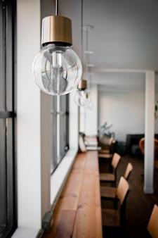 Hang light bulb near glass window over wooden bar