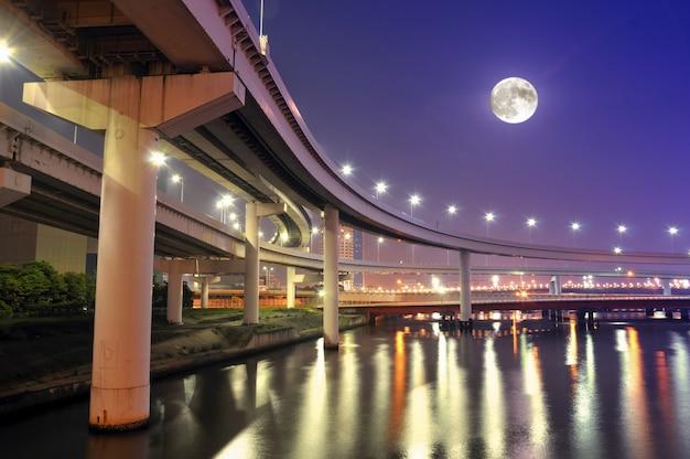 満月が空に浮かぶ夜の東京湾の水上に吊るされた高速道路