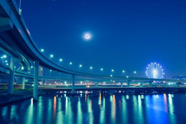 月と観覧車のイルミネーションが後方にある、夜間の東京湾の水上に吊るされた高速道路