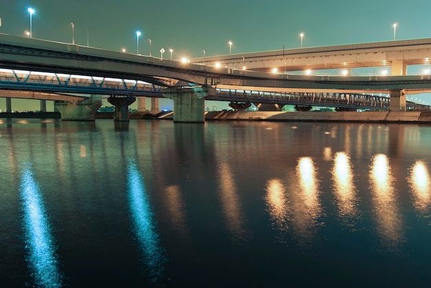Hanged up highways over river waters by night in tokyo
