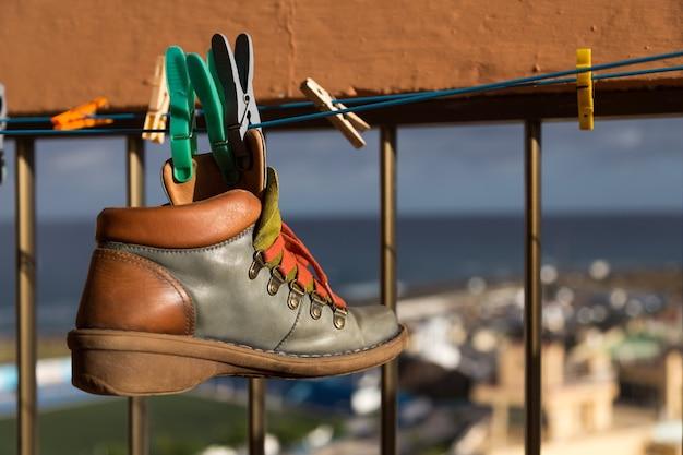 Подвешенный прищепками кожаный ботинок сушится на бельевой веревке в солнечный день. выборочный фокус.