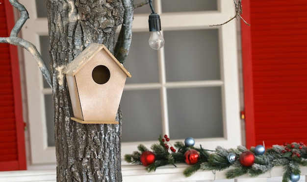 Hanged wooden bird house or nist on tree in decorated house garden