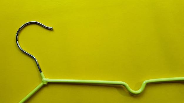 노란색 배경에 옷 걸이입니다. 녹색 옷걸이. 복사 공간이 있는 배경. 블랙 프라이데이, 쇼핑의 날