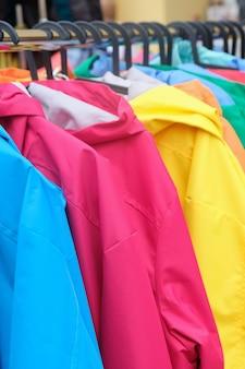 ファッショナブルな異なる色のジャケットを販売している店のハンガー。