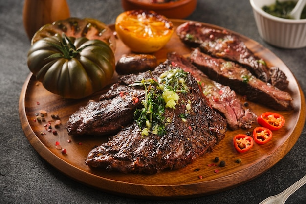Hanger steak bbq with souce chimichurri on wooden plate, close up.
