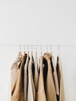 A hanger of warm beautiful feminine beige sweaters or pullovers