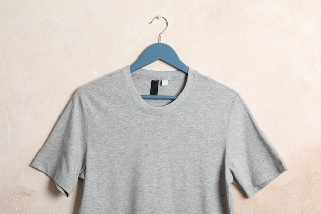Hanger with blank gray t-shirt on light brown