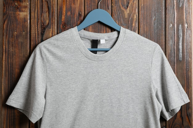Hanger with blank gray t-shirt on wooden