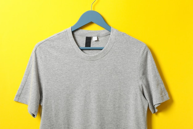 Hanger with blank gray t-shirt on yellow