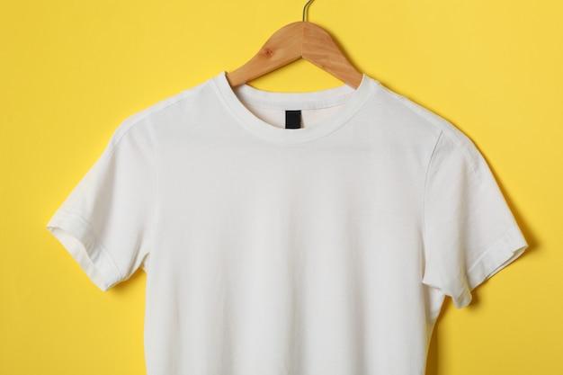 Вешалка с пустой белой футболкой на желтом