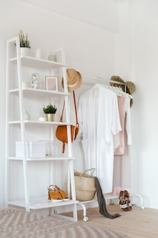 Hanger with clothes in trendy pastel colour on a rack with accessories