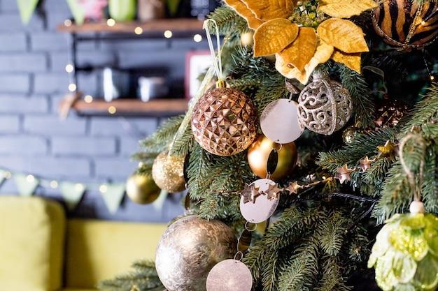 クリスマスツリーの枝にキラキラ光る渦巻きとつまらないものをぶら下げます。選択的な焦点、ヴィンテージまたは