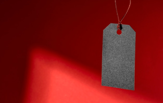 Hanging black price tag on red background copy space