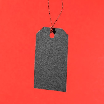 Hanging black price tag on red background