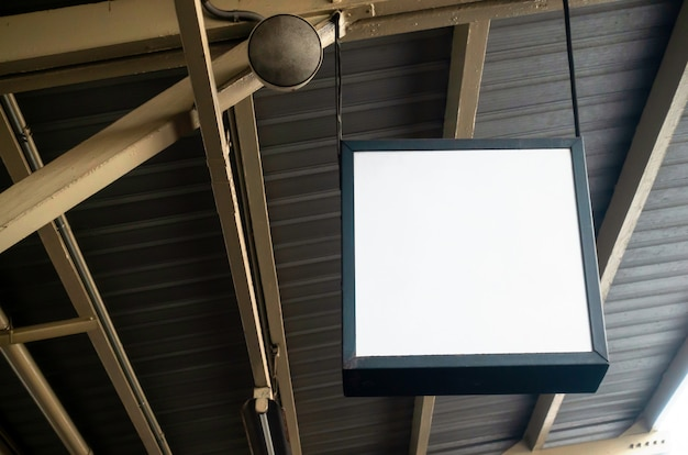 Hanging blank advertising billboard or light box showcase on wall at airport or subway train station