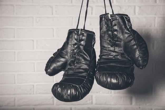 Боксерские перчатки висит на фоне кирпичной стены