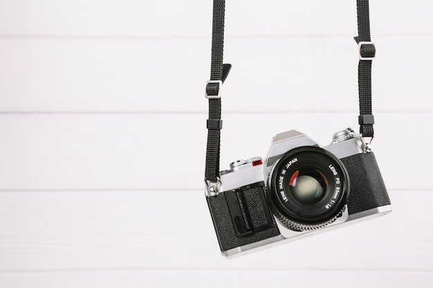 Hanging camera in front of white background