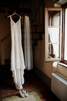 Hanging classy wedding dress and wedding veil in the room near the opened window