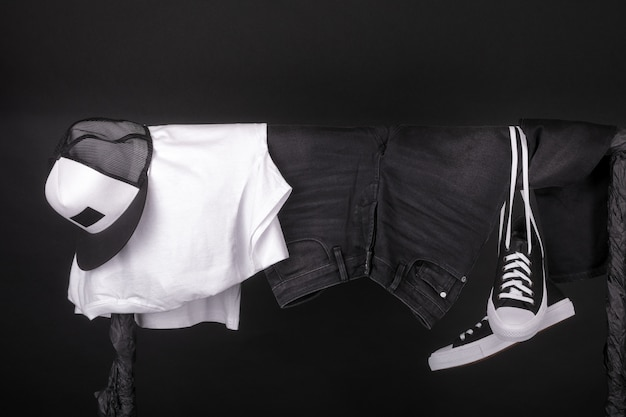 Hanging clothing. black and white sneakers, cap and jeans on clothes rack on black.