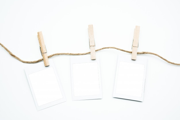 Hanging empty polaroid photo frame on rod with clipping path