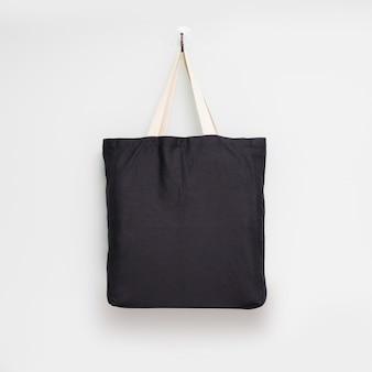흰 벽 배경에 매달려 패브릭 가방.