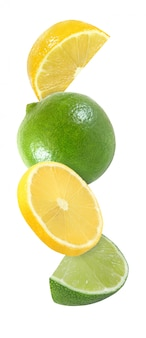 Hanging, falling, flying piece of lemon and lime fruits isolated on white background with clipping path