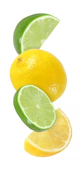 Hanging, falling, flying piece of lime and lemon fruits isolated on white background with clipping path