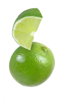 Hanging, falling, hovering, flying piece of lime fruits isolated on white background with clipping path