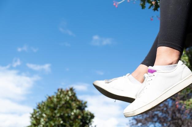 コピースペースと背景の美しい自然のシナリオで女の子のスニーカーの空と足をぶら下げ