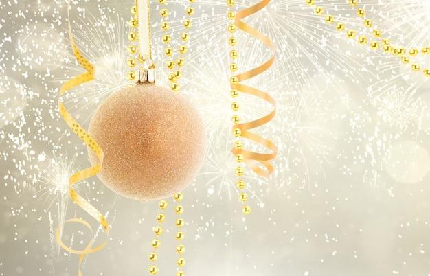 Висячий золотой елочный шар с гирляндами на серебряном фоне боке