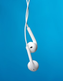Hanging headphones on a white cable, a modern gadget on a blue background