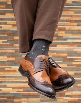 エレガントな靴で男の足をぶら下げ