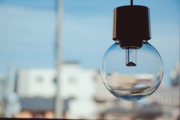 Hanging light bulb near glass window