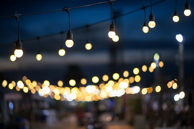 Hanging light bulbs with blur bokeh at night of outdoor shopping mall.